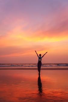 Vrouw met opgeheven handen voelt vrijheid en geniet van goa-zonsondergang