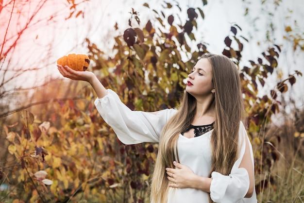 Vrouw met oranje pompoen poseren in de buurt van herfst bomen