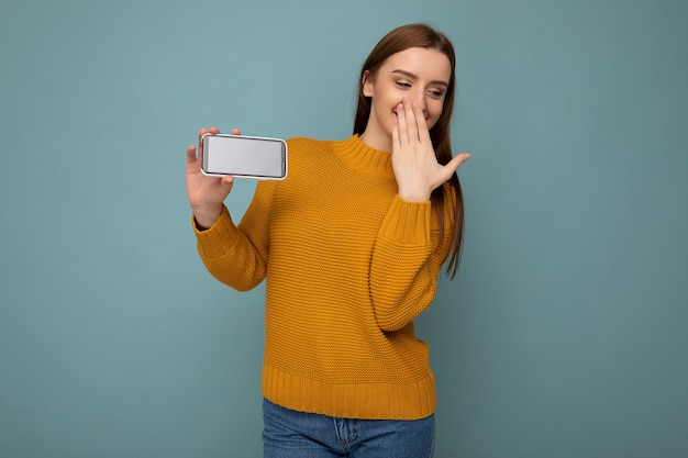 Vrouw met oranje trui in evenwicht geïsoleerd op blauwe muur met lege ruimte in de hand te houden en mobiele telefoon met lege ruimte te tonen