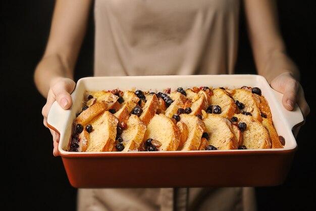 Vrouw met ovenschaal met lekkere broodpudding op donkere achtergrond