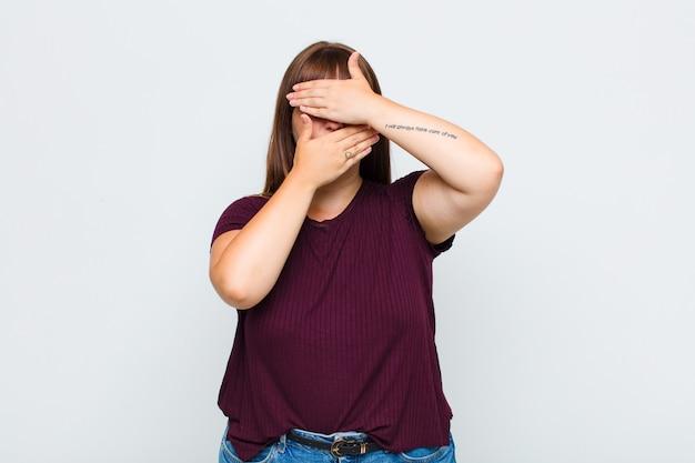 Vrouw met overgewicht bedekt gezicht met beide handen en zegt nee! afbeeldingen weigeren of foto's verbieden