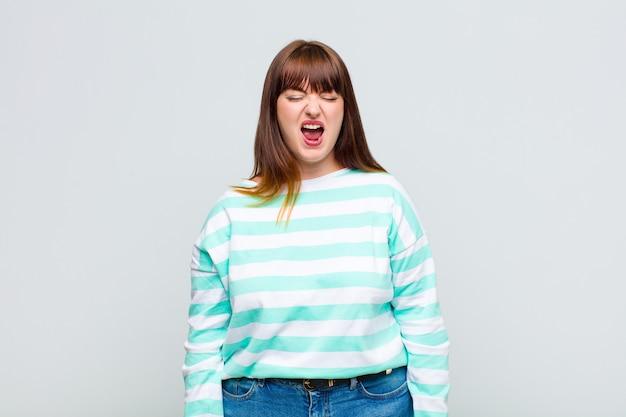 Vrouw met overgewicht die agressief schreeuwt, er erg boos, gefrustreerd, verontwaardigd of geïrriteerd uitziet, nee schreeuwt