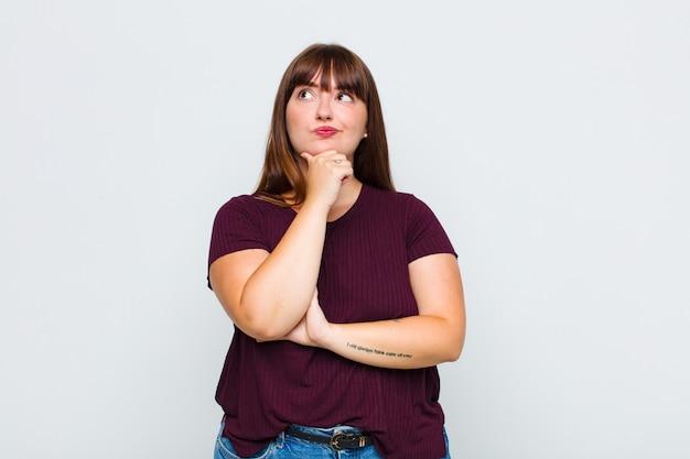 Vrouw met overgewicht die denkt, zich twijfelachtig en verward voelt, met verschillende opties, zich afvraagt welke beslissing ze moet nemen