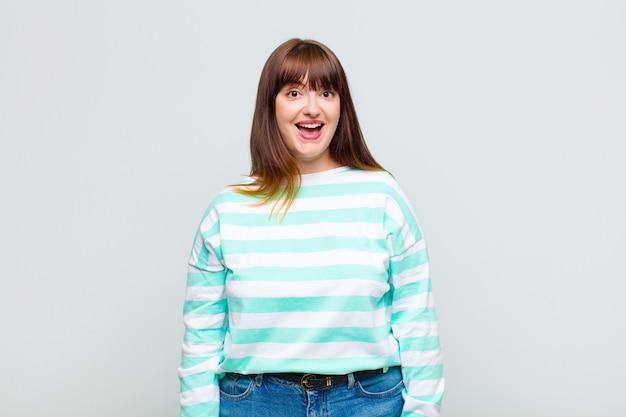 Vrouw met overgewicht die er blij en aangenaam verrast uitziet, opgewonden met een gefascineerde en geschokte uitdrukking