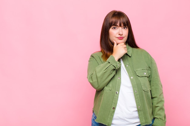 Vrouw met overgewicht die er serieus, verward, onzeker en attent uitziet, twijfelt tussen opties of keuzes