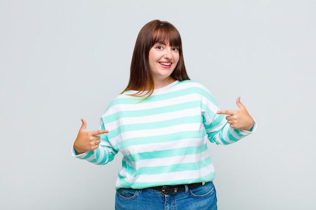 Vrouw met overgewicht die er trots, arrogant, blij, verrast en tevreden uitziet, naar zichzelf wijst en zich een winnaar voelt