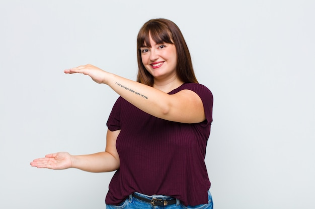 Vrouw met overgewicht die glimlacht, zich gelukkig, positief en tevreden voelt, voorwerp of concept op exemplaarruimte vasthoudt of toont