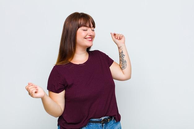 Vrouw met overgewicht die lacht, zich onbezorgd, ontspannen en gelukkig voelt, danst en naar muziek luistert, plezier heeft op een feestje