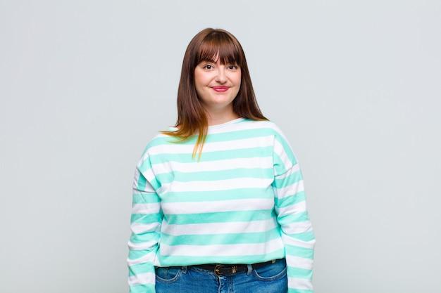Vrouw met overgewicht die positief en zelfverzekerd glimlacht, er tevreden, vriendelijk en gelukkig uitziet