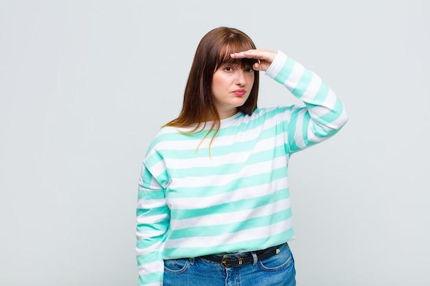 Vrouw met overgewicht die verbijsterd en verbaasd kijkt, met de hand over het voorhoofd ver weg kijkend, toekijkend of zoekend