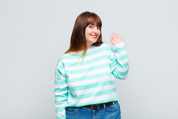 Vrouw met overgewicht die vrolijk en opgewekt glimlacht, hand zwaait, u verwelkomt en begroet, of afscheid neemt
