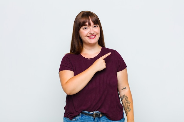 Vrouw met overgewicht die vrolijk glimlacht, zich gelukkig voelt en naar de zijkant en naar boven wijst, object in kopie ruimte toont