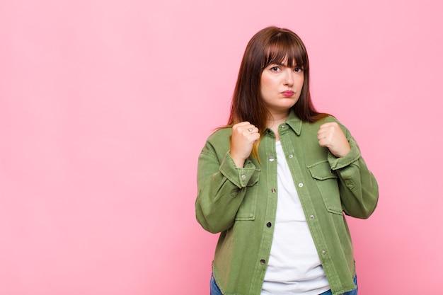 Vrouw met overgewicht die zelfverzekerd, boos, sterk en agressief kijkt, met vuisten klaar om te vechten in bokspositie