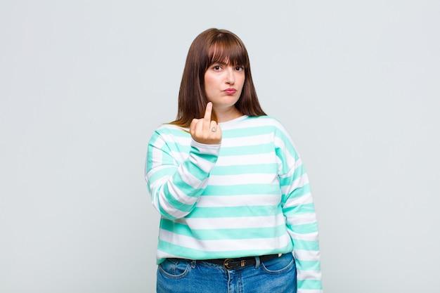 Vrouw met overgewicht die zich boos, geïrriteerd, rebels en agressief voelt, de middelvinger omdraait, terugvecht