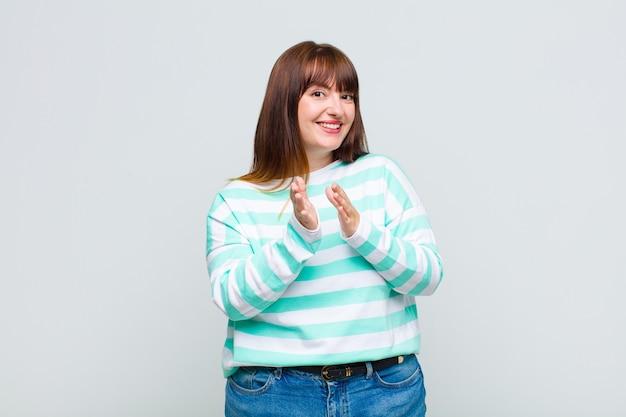Vrouw met overgewicht die zich gelukkig en succesvol voelt, lacht en klapt in de handen, feliciteert met een applaus