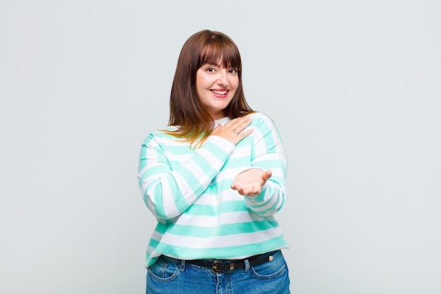 Vrouw met overgewicht die zich gelukkig en verliefd voelt, glimlachend met de ene hand naast het hart en de andere naar voren gestrekt