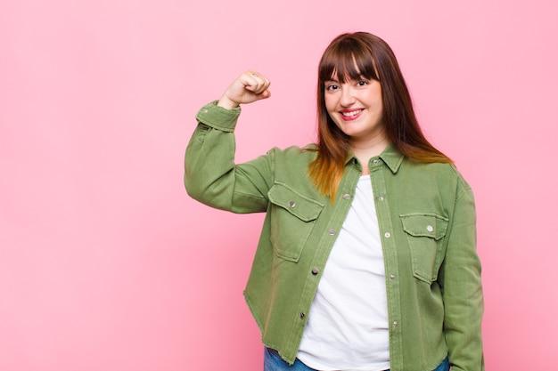Vrouw met overgewicht die zich gelukkig, tevreden en krachtig voelt, buigzaam fit en gespierde biceps, die er sterk uitziet na de sportschool