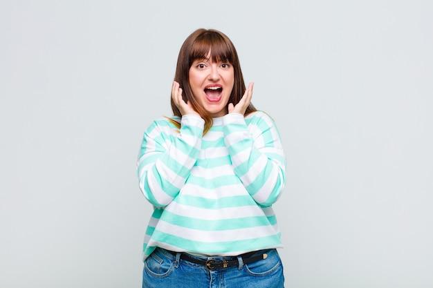 Vrouw met overgewicht die zich geschokt en opgewonden voelt, lacht, verbaasd en blij is vanwege een onverwachte verrassing