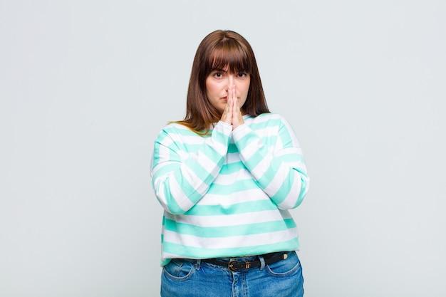 Vrouw met overgewicht die zich ongerust, hoopvol en religieus voelt, trouw bidt met de handpalmen ingedrukt, smekend om vergeving
