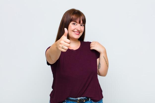 Vrouw met overgewicht die zich trots, zorgeloos, zelfverzekerd en gelukkig voelt en positief glimlacht met de duimen omhoog