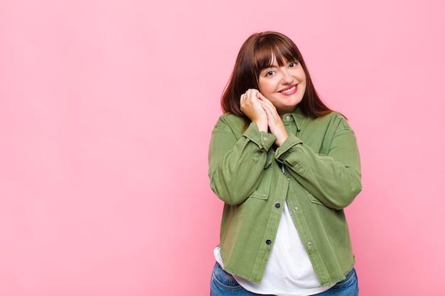 Vrouw met overgewicht die zich verliefd voelt en er schattig, schattig en gelukkig uitziet, romantisch glimlachend met de handen naast het gezicht