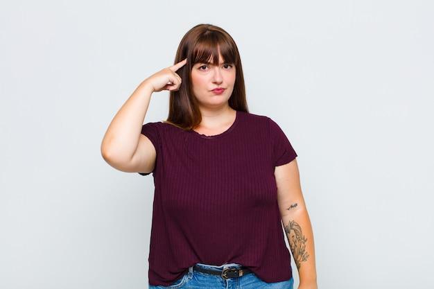 Vrouw met overgewicht die zich verward en verbaasd voelt, laat zien dat u gek, gek of gek bent