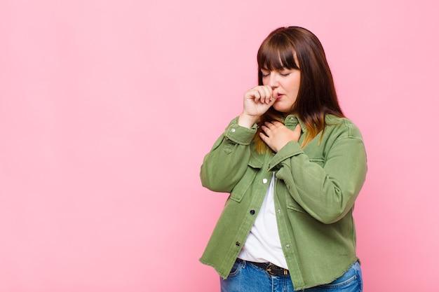 Vrouw met overgewicht die zich ziek voelt met keelpijn en griepsymptomen, hoesten met bedekte mond