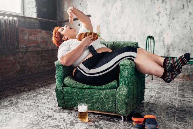 Vrouw met overgewicht eet sandwich, boulimisch, obesitasprobleem. ongezonde levensstijl, vette vrouw