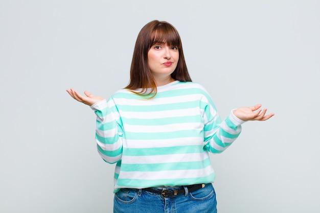 Vrouw met overgewicht kijkt verbaasd, verward en gestrest, vraagt zich af tussen verschillende opties, voelt zich onzeker