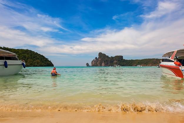 Vrouw met overgewicht komt in zee om te zwemmen bekijk het zandstrand van de phi phi-eilanden met golven