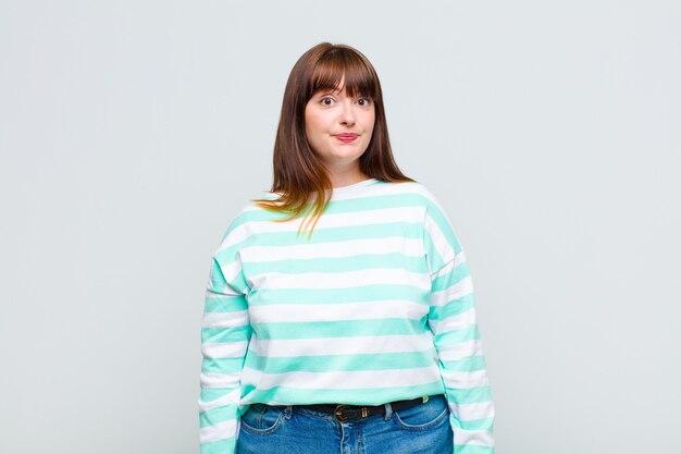 Vrouw met overgewicht met een gekke, gekke, verbaasde uitdrukking, puffende wangen, zich gevuld, dik en vol eten