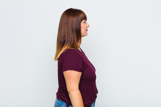 Vrouw met overgewicht op profielweergave die ruimte vooruit wil kopiëren, denken, zich voorstellen of dagdromen