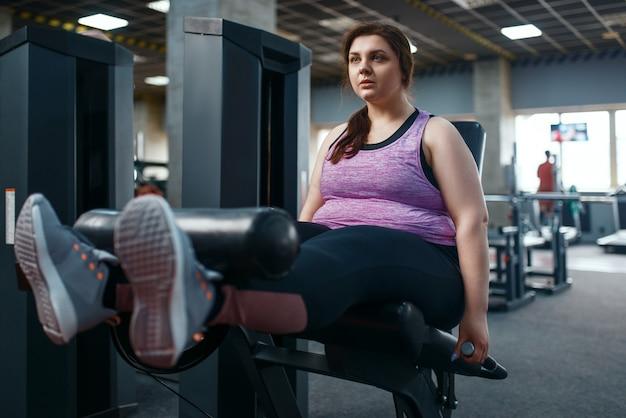Vrouw met overgewicht pompt pers, oefening in de sportschool, actieve training