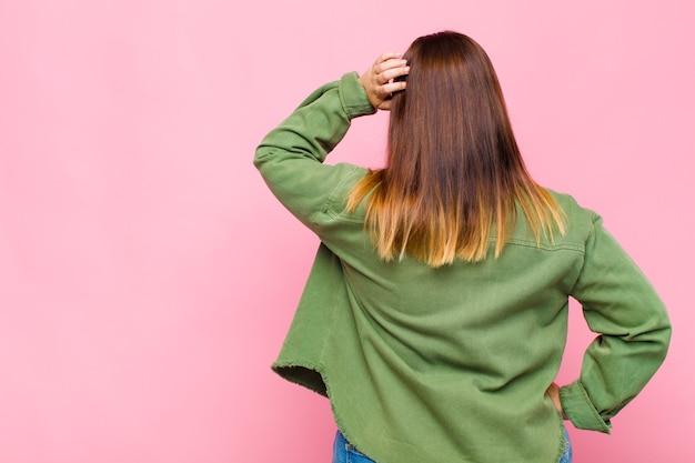 Vrouw met overgewicht voelt zich geen idee en verward, denkt een oplossing, met de hand op de heup en de andere op het hoofd, zicht naar achteren