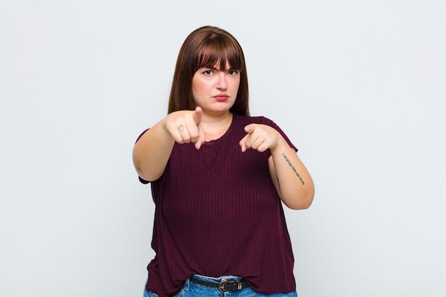 Vrouw met overgewicht wijzend met beide vingers en een boze uitdrukking, die u zegt uw plicht te doen