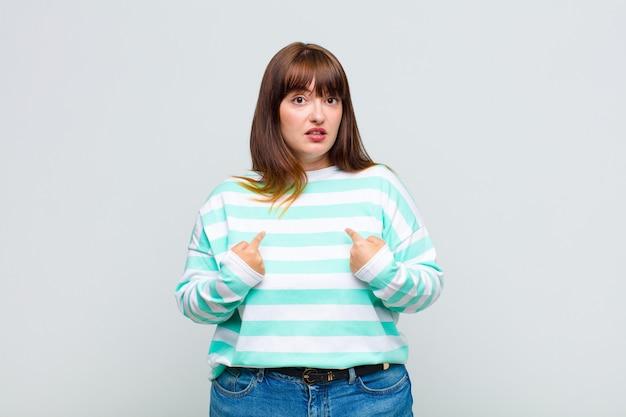 Vrouw met overgewicht wijzend naar zichzelf met een verwarde en vragende blik, geschokt en verrast om gekozen te worden