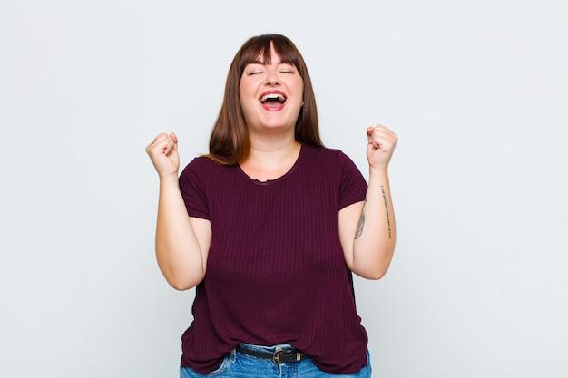 Vrouw met overgewicht ziet er buitengewoon blij en verrast uit, viert succes, roept en springt
