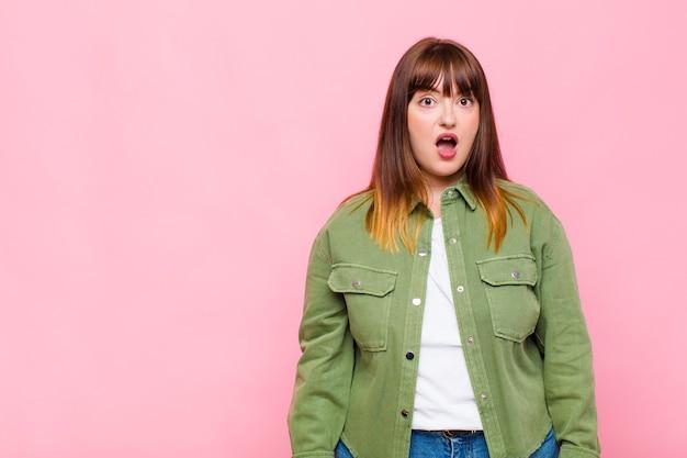 Vrouw met overgewicht ziet er erg geschokt of verrast uit, staart met open mond en zegt wow