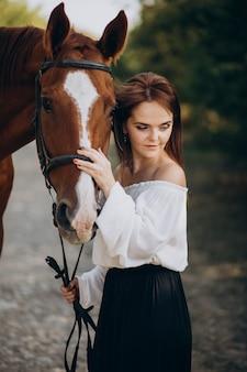 Vrouw met paard in bos