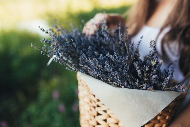 Vrouw met paarse lavendel bloemen in de houten doos