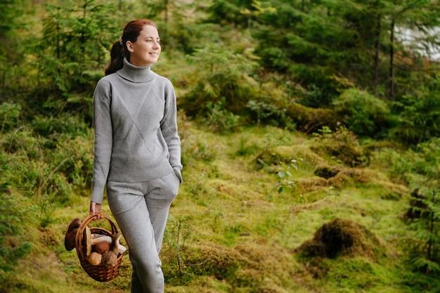 Vrouw met paddenstoelen in een rieten mand die door het bos loopt concept van het oogstseizoen