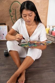 Vrouw met palet en schilderij penseel