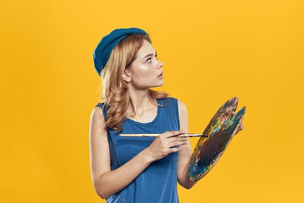 Vrouw met palet in blauwe handen neemt het kunstwerk van de penseelhobby geel