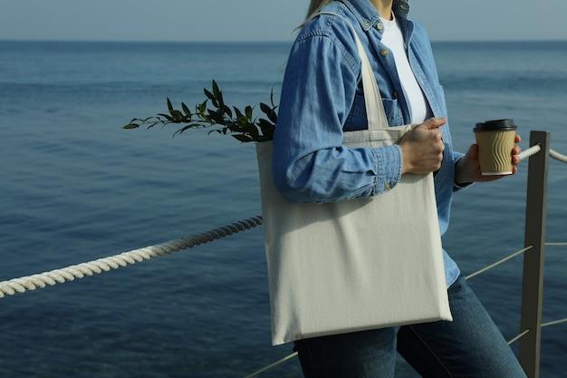 Vrouw met papieren beker en eco tas staande op de pier tegen zee