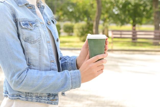 Vrouw met papieren koffiekopje in park Premium Foto
