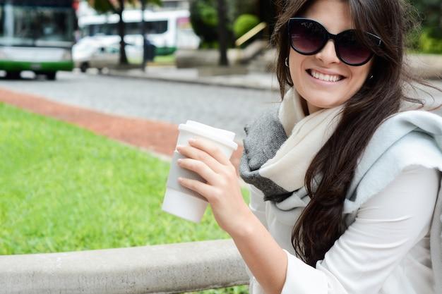 Vrouw met papieren kopje koffie in de straat.