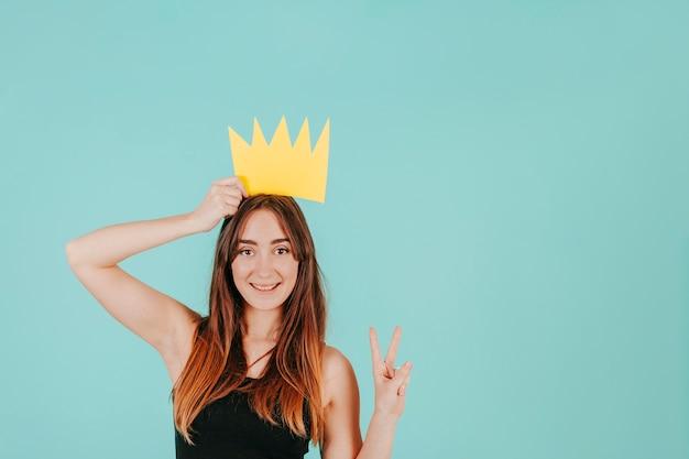 Vrouw met papieren kroon gesturing vrede