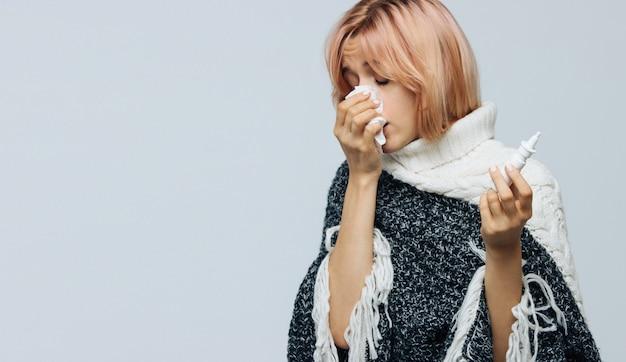 Vrouw met papieren servet niezen, met behulp van neusspray om zichzelf te helpen. allergie, griep