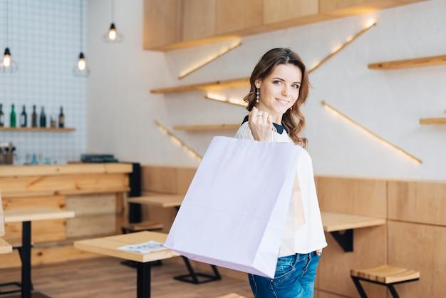 Vrouw met papieren zakken in café