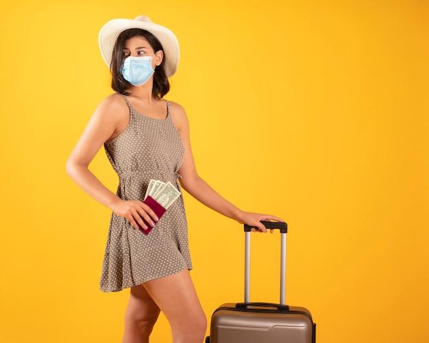 Vrouw met paspoort en koffer, die een masker draagt